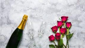 香宾瓶和玻璃与小组玫瑰 免版税库存照片