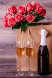 香宾,玫瑰色和一则可爱的消息在桌上 库存图片
