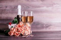 香宾,玫瑰色和一则可爱的消息在桌上 免版税图库摄影