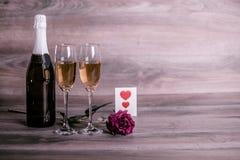 香宾,玫瑰色和一则可爱的消息在桌上 库存照片
