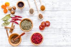 香料和干草本品种在碗在轻的木厨房用桌背景顶视图大模型 库存照片