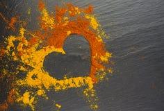 从香料咖喱和辣椒粉的华伦泰心脏在黑背景 2月14日 库存照片