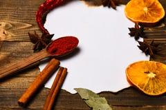香料,厨房草本在白皮书附近放置 烹饪食谱概念 桂香、干桔子和胡椒,八角位置 免版税库存图片