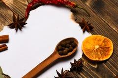 香料,厨房草本在白皮书附近放置 烹饪食谱概念 肉桂条、干桔子和八角位置 免版税库存图片