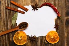 香料,厨房草本在白皮书附近放置 肉桂条、干桔子和八角在白纸附近放为 免版税图库摄影