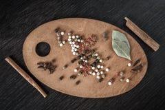 香料,黑胡椒,桂香,在卵形木板黑暗backgr的月桂叶 免版税库存图片