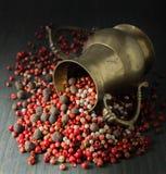 香料;白色的胡椒,桃红色,在黑暗的背景的黑,有气味,黄铜水罐 免版税库存照片