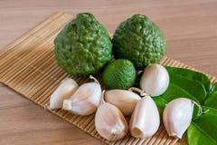 香柠檬和大蒜在makisu席子在木纹理 免版税库存照片