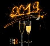 香槟和新年2019金黄数字玻璃写与闪闪发光烟花在黑色 免版税库存图片