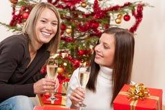 香槟圣诞树二妇女年轻人 免版税库存照片
