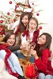 香槟圣诞节四个敬酒妇女年轻人 免版税库存照片