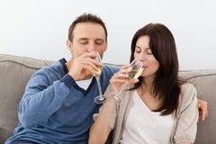 香槟夫妇饮用的轻松的沙发 免版税库存照片