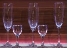 香槟的玻璃和杯在木纹理的背景的透明玻璃 免版税图库摄影