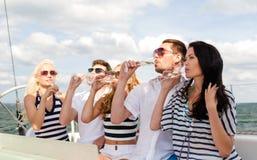 戴香槟眼镜的微笑的朋友在游艇的 库存照片