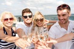 戴香槟眼镜的微笑的朋友在游艇的 免版税库存图片