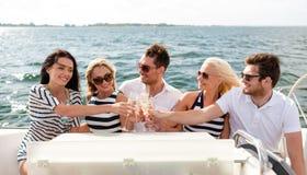 戴香槟眼镜的微笑的朋友在游艇的 免版税图库摄影