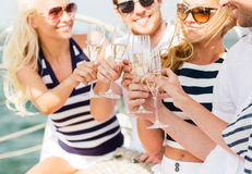 戴香槟眼镜的愉快的朋友在游艇的 免版税库存图片