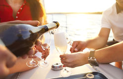 戴香槟眼镜的愉快的朋友在游艇的 免版税库存照片