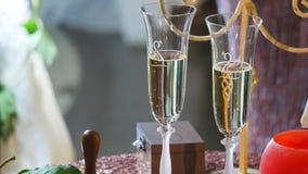 香槟装饰了婚姻装饰花的玻璃 溢出香宾到玻璃里 欢乐酒精 新娘和新郎的杯 结构婚礼 影视素材