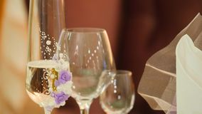 香槟装饰了婚姻装饰花的玻璃 溢出香宾到玻璃里 欢乐酒精 新娘和新郎的杯 结构婚礼 股票视频