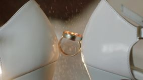 香水在新娘之间被安置的定婚戒指浪花婚姻鞋子 关闭 宏观慢动作 影视素材