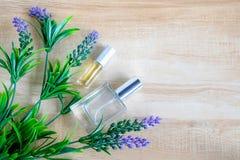 香水瓶和紫色花 免版税库存图片