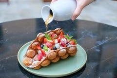 香港样式奶蛋烘饼用莓果和鲜美果子与蜂蜜倾吐 免版税库存照片