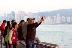 香港江边:在黄昏的人拍摄的日落 免版税库存图片