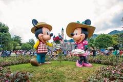 香港迪斯尼乐园- 2015年5月:Mickey和minnie在爱在公园在城堡前面 图库摄影