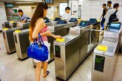 香港,中国- 2015年5月:女孩通过在地铁的旋转门 库存照片