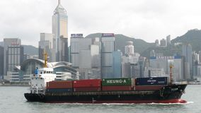 香港,中国- 2018年8月15日:横渡维多利亚habour和市地平线的小集装箱船 股票视频