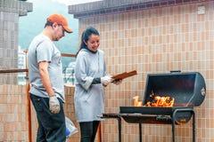 香港,中国- 2016年1月17日:白种人男人和亚裔妇女年轻夫妇点燃在烤肉的火 室外烤肉cooki 免版税库存照片