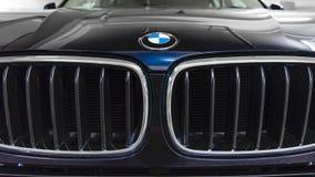 香港,香港- 2018年4月25日:BMW商标徽章特写镜头和署名汽车在蓝色BMW跑车烤 库存照片