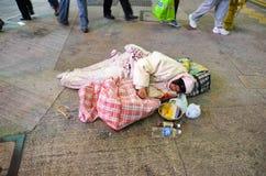 香港,香港- 2013年12月8日:在街道上的一个未认出的妇女睡眠者 免版税图库摄影