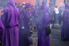 香火的两个年轻紫色着长袍的人抽烟在圣Bartolome在1a Avenida,安提瓜岛的de Becerra队伍  免版税图库摄影