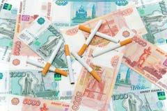 香烟和卢布。 消耗大的习性。 库存图片
