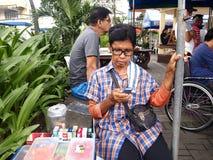 香烟和糖果供营商使用她的手机 库存照片