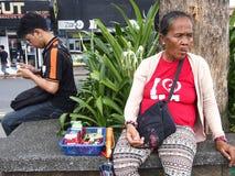 香烟和糖果供营商在她的产品旁边坐 库存图片