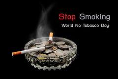 香烟烧与烟和硬币在烟灰缸在黑暗 库存图片
