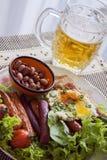 香肠和烤鸡胸脯和杯啤酒 库存图片