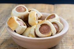 香肠在新月形面包面团被烘烤的冷却滚动了在金属机架 免版税图库摄影