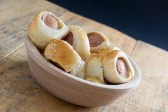 香肠在新月形面包面团被烘烤的冷却滚动了在金属机架 图库摄影