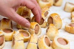 香肠在新月形面包面团被烘烤的冷却滚动了在金属机架 免版税库存图片