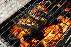 香肠烤与与火的灼烧的木炭在与格栅的火炉在上面在曼谷,泰国 免版税库存图片