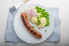 香肠用饲料和有些豌豆 免版税库存照片