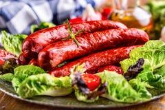香肠 加调料的口利左香肠香肠 与菜装饰的未加工的熏制的香肠 莴苣沙拉草本迷迭香蕃茄大蒜橄榄油 库存照片