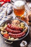 香肠 格栅香肠 烤香肠用啤酒采蘑菇大蒜蕃茄和葱 免版税图库摄影