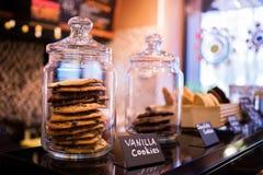 香草曲奇饼块菌用在玻璃瓶子的巧克力在咖啡馆的架子 免版税库存图片