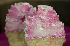 香草杯形蛋糕冠上了与桃红色和白色结霜 免版税库存图片