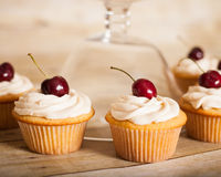 香草杯形蛋糕用黄油提取乳脂结霜和一棵樱桃在上面 库存图片